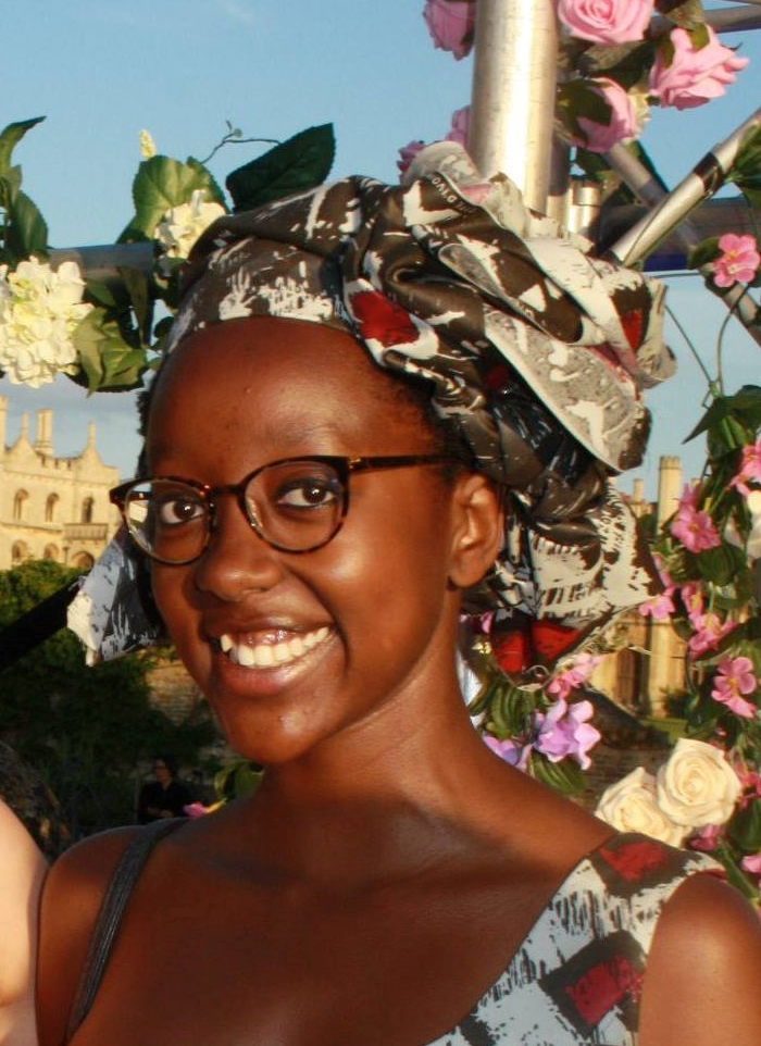 Photograph of Waithera Sebatindira the first black woman to ever have held the position of CUSU (Cambridge university students union) women's Officer. She looks directly and the camera and smiles