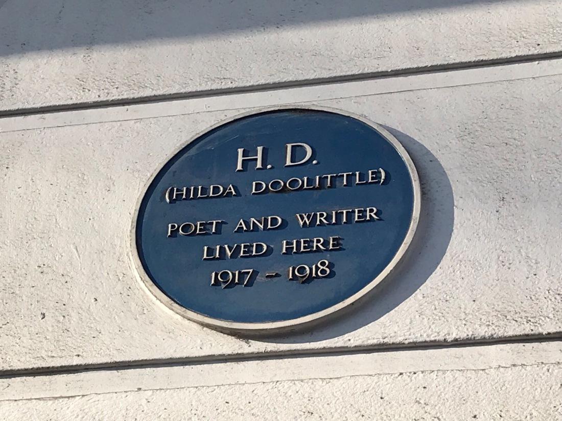 Blue Plaque commemorating bisexual trailblazing female poet H.D. - Hilda Doolittle, a feminist inspiration. Plaque is in Camden